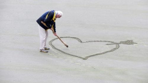 砂浜にハートマークを書く紳士